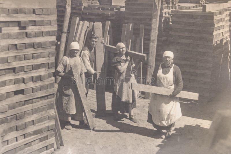 РОССИЯ - ОКОЛО 1920s: Винтажное фото молодых женщин и человека thee работая в изготовлении стоковое изображение