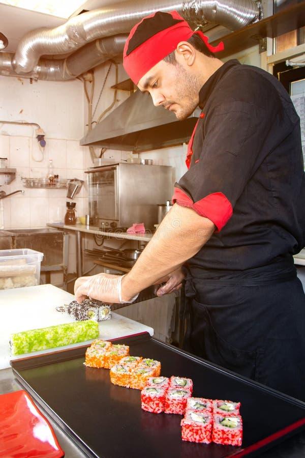 Россия, Рязань - 12 11 2018 - Усмехаясь азиатский шеф-повар с сушами на кухне стоковая фотография rf