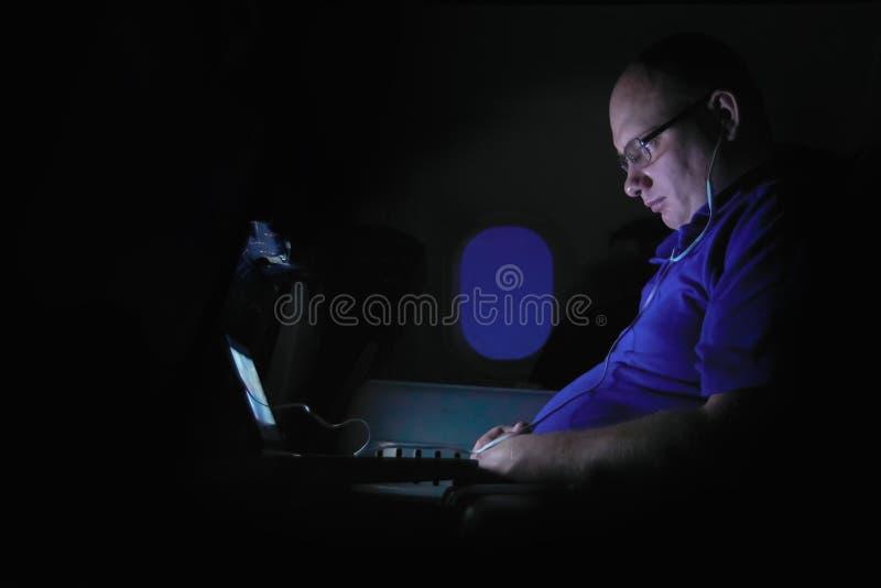 РОССИЯ, САЛОН Боинг 747 ВОЗДУШНЫХ СУДН, НОЧА 8-ое февраля 2018 - бизнесмен работает на ноче на компьтер-книжке в кабине самолет стоковое фото