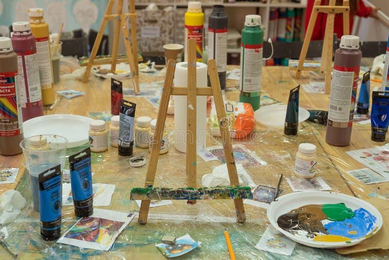 Россия, Татарстан, 21-ое апреля 2019 Грязная таблица в краске художника после рисовать Мольберт, краска, палитра, щетки на таблиц стоковые фото