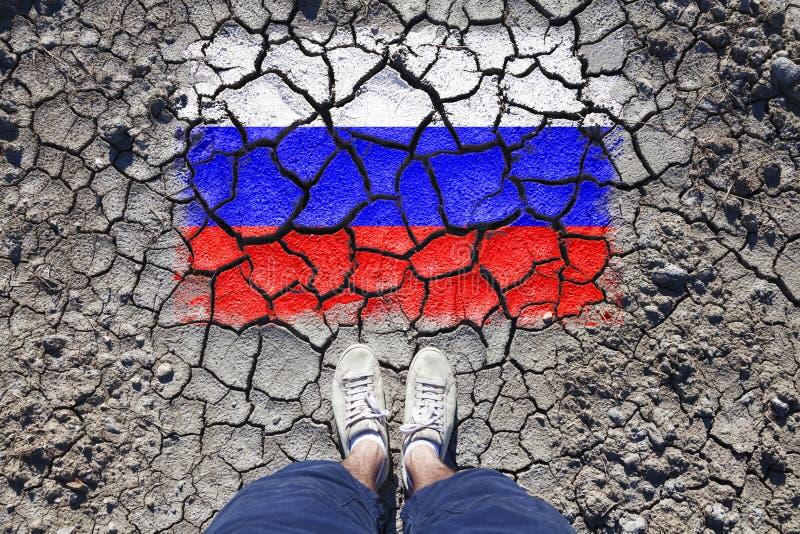Россия треснула флаг с ногами человека стоковая фотография rf