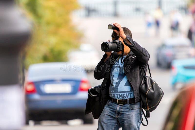 Россия, Rostov On Don, 9-ое сентября 2018: Профессиональный фотограф снимает фото с камерой Nikon DSLR с электрофонарем и объекти стоковые изображения