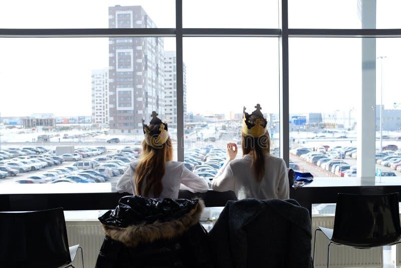 Россия, Tyumen, 30 03 2019 Девочка-подростки в кронах от Burger King на обед на торговом центре Девушки едят в торговом центре За стоковые фото