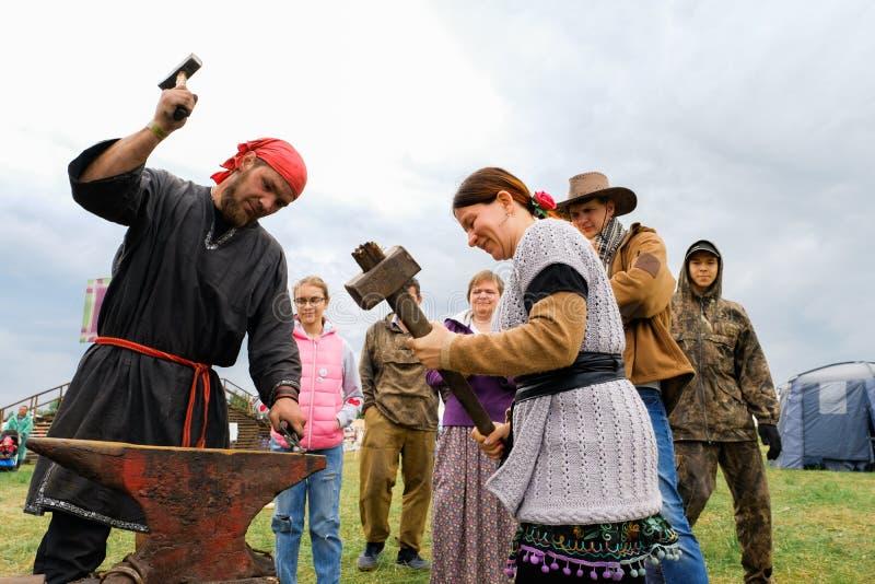 Россия, Tyumen, 15 06 2019 Кузнец держит мастерский класс на ковать на фестивале различных наций Ударьте молоток на стоковое изображение rf