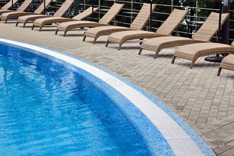 Ротанг Sunbeds Poolside гостиницы пустой около списка избирателей заплывания стоковые изображения