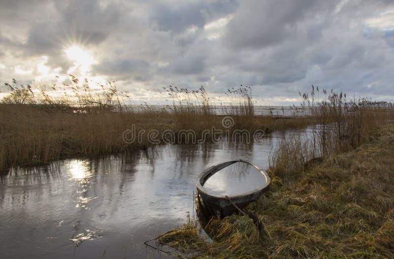 Рот реки с утонул шлюпка на заход солнца стоковая фотография rf