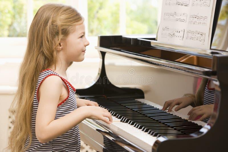 рояль девушки играя детенышей стоковое фото