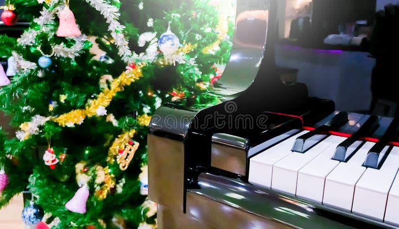 Рояль и блеск, который нужно играть главные роли с рождественской елкой стоковые фотографии rf