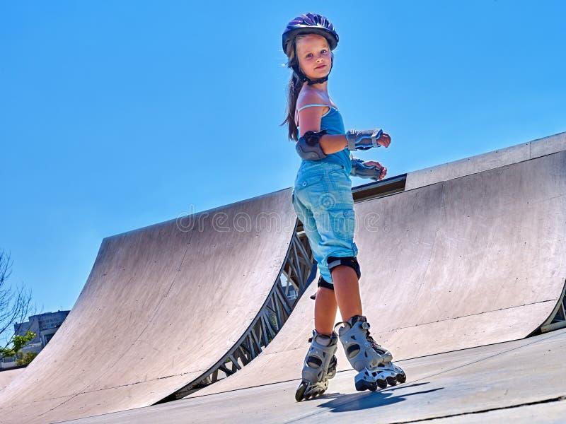 Ролик девушки в парке коньков Шлем безопасности носки ребенка резвится тренировка стоковые фото
