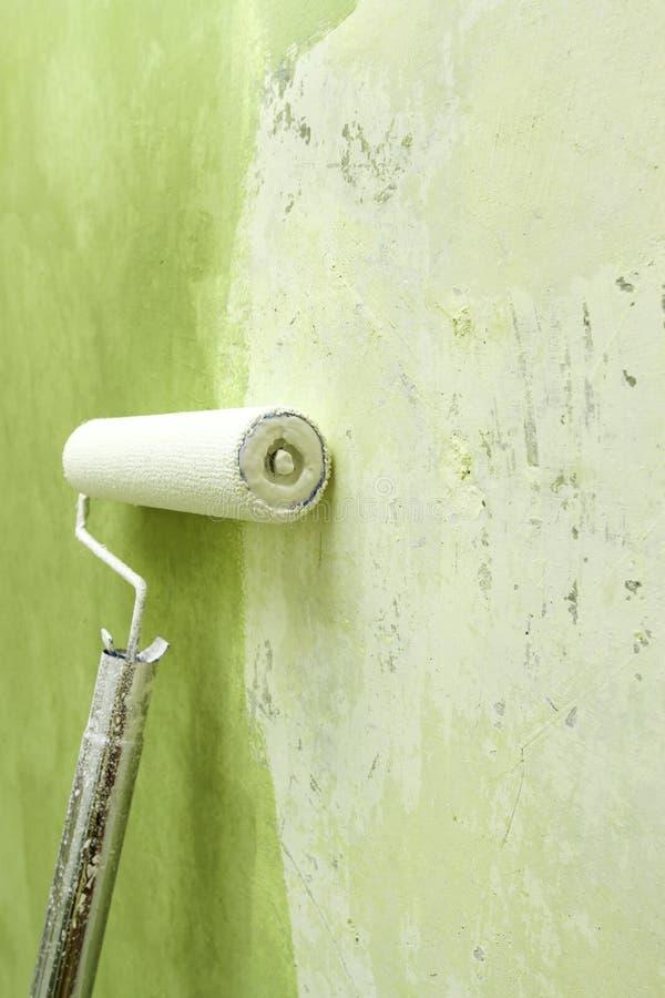 Ролик краски прикладывая краску на белой стене, улучшениях дома стоковое фото rf
