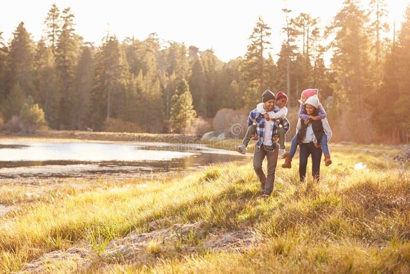 Родители давая детям езду автожелезнодорожных перевозок на прогулке озером стоковое фото rf