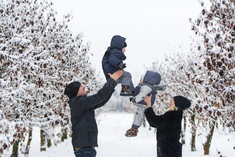 Родители бросают детей вверх стоковое фото