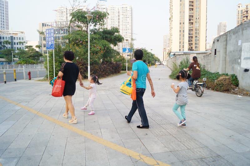 Родители детского сада выбирают вверх детей идут домой после школы, стоковая фотография rf