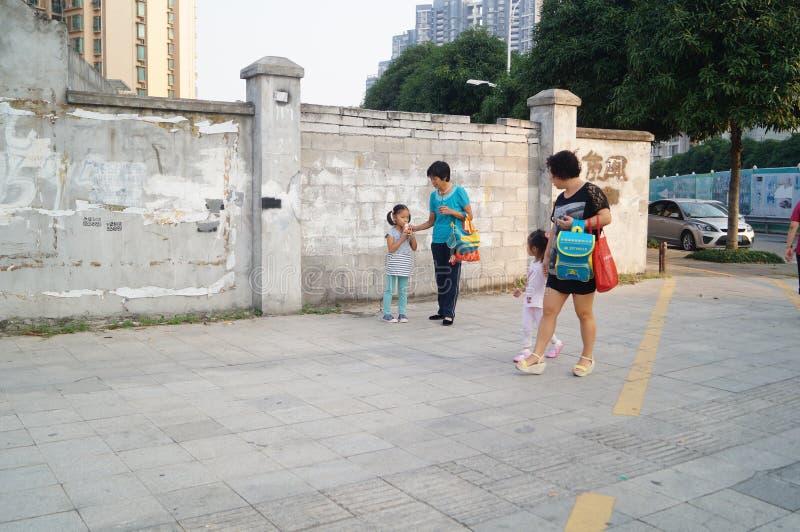 Родители детского сада выбирают вверх детей идут домой после школы, стоковые фотографии rf