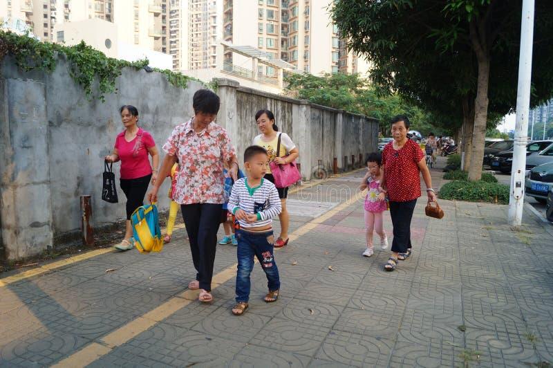 Родители детского сада выбирают вверх детей идут домой после школы, стоковое изображение
