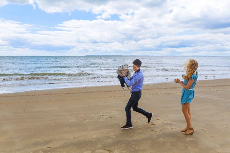 Родители играя с его сыном на пляже стоковая фотография