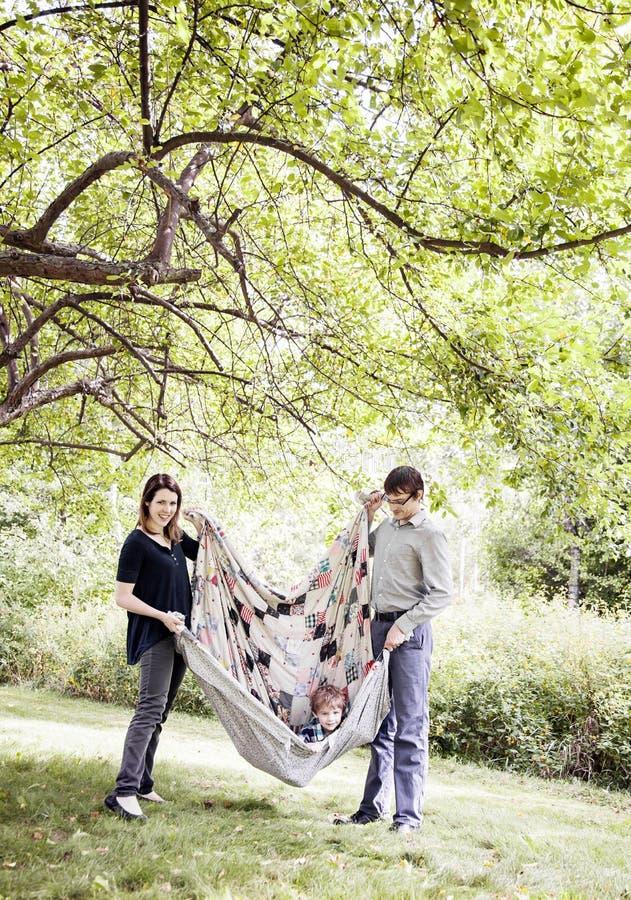 Родители играя с ребенком в одеяле стоковая фотография
