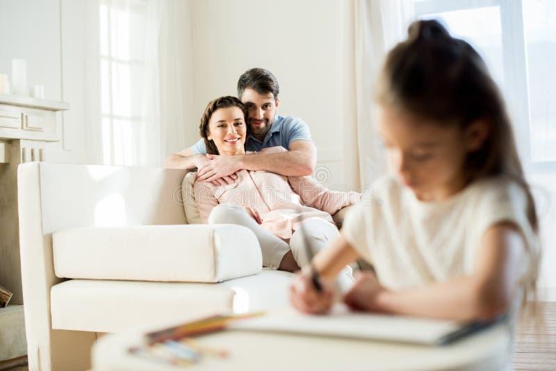 Родители наблюдая, как чертеж дочери изобразил дома стоковые фотографии rf