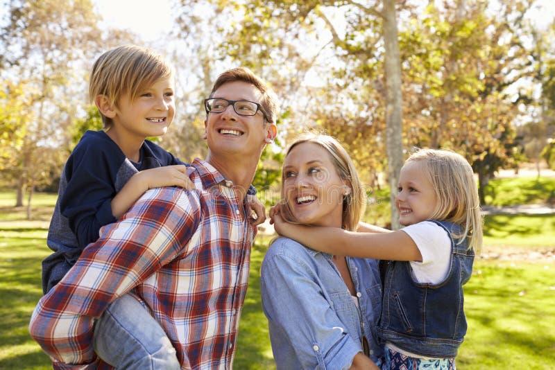 Родители нося 2 молодого парня в повороте парка для того чтобы посмотреть сына стоковая фотография rf