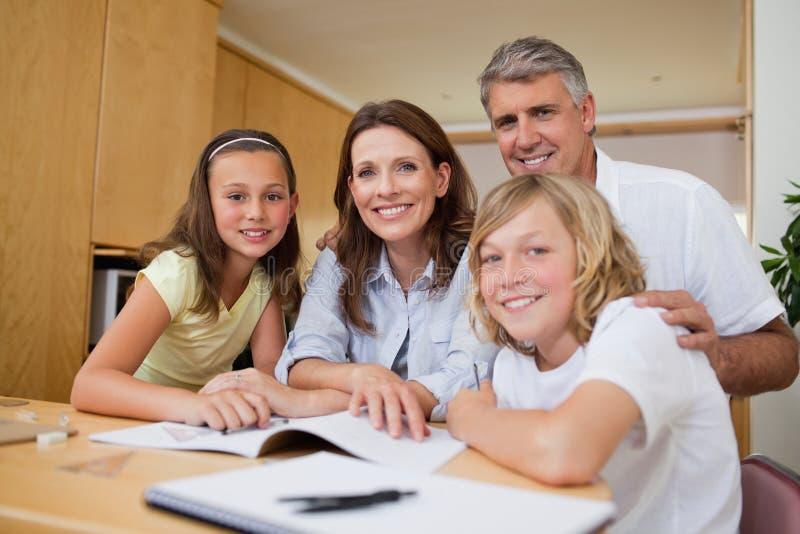 Родители помогая их детям с домашней работой стоковое изображение rf
