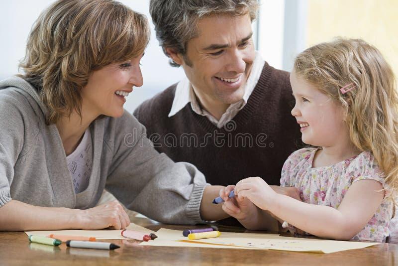 Родители помогая их дочери нарисовать бесплатная иллюстрация