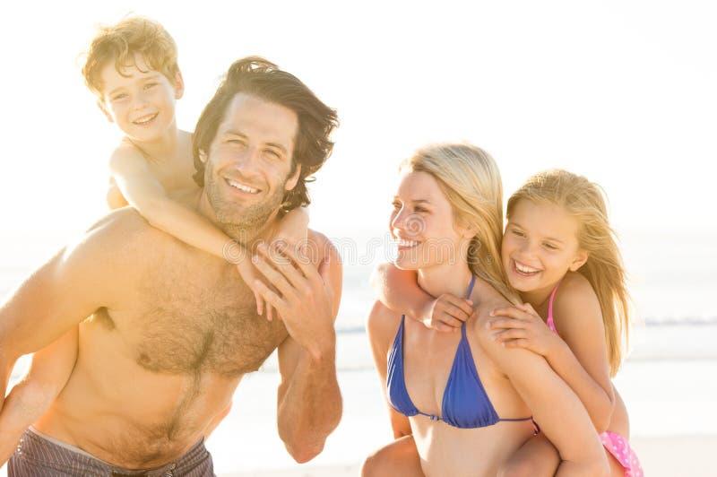 Родители с детьми на пляже стоковая фотография