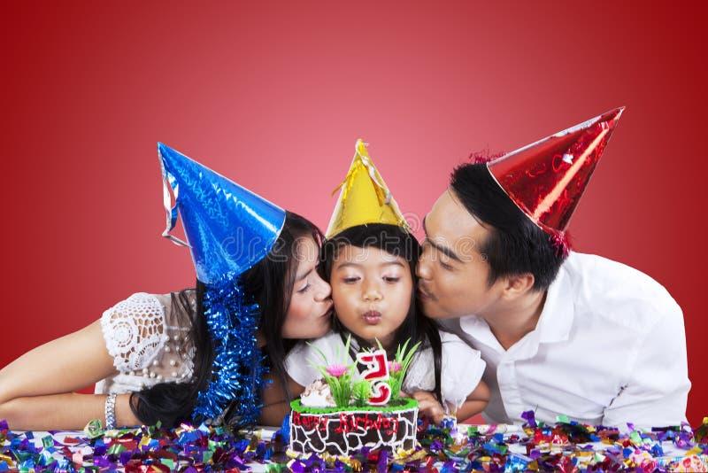 Родители целуют их ребенка в вечеринке по случаю дня рождения стоковое фото rf