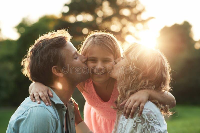 Родители целуя их усмехаясь маленькую девочку на ее щеках снаружи стоковое фото rf