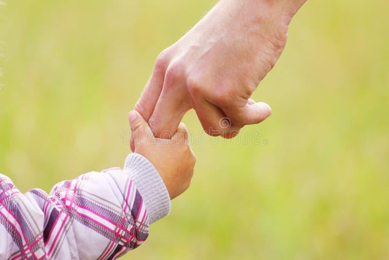 Родитель держит руку малого ребенка стоковое изображение rf