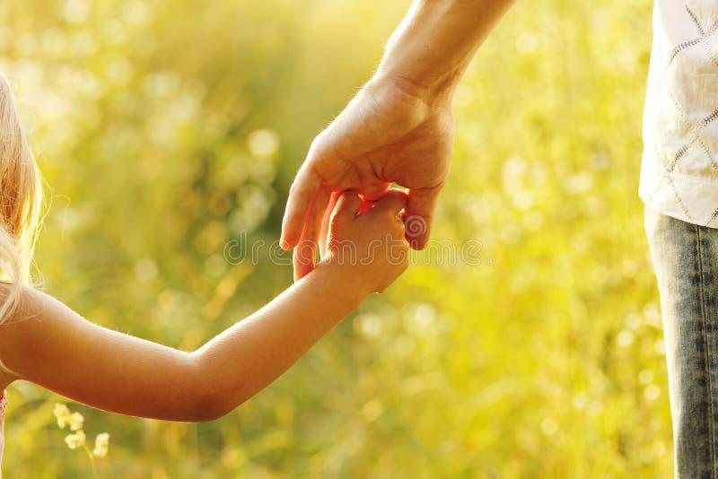 Родитель держит руку малого ребенка стоковое фото rf
