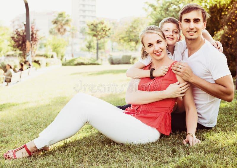 Родитель с мальчиком в предназначенном для подростков времени сидя на зеленой траве в парке стоковое фото rf