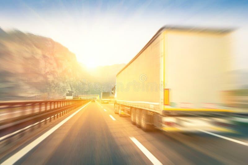 Родовой semi перевозит быстро проходить на грузовиках на шоссе на заходе солнца стоковое фото