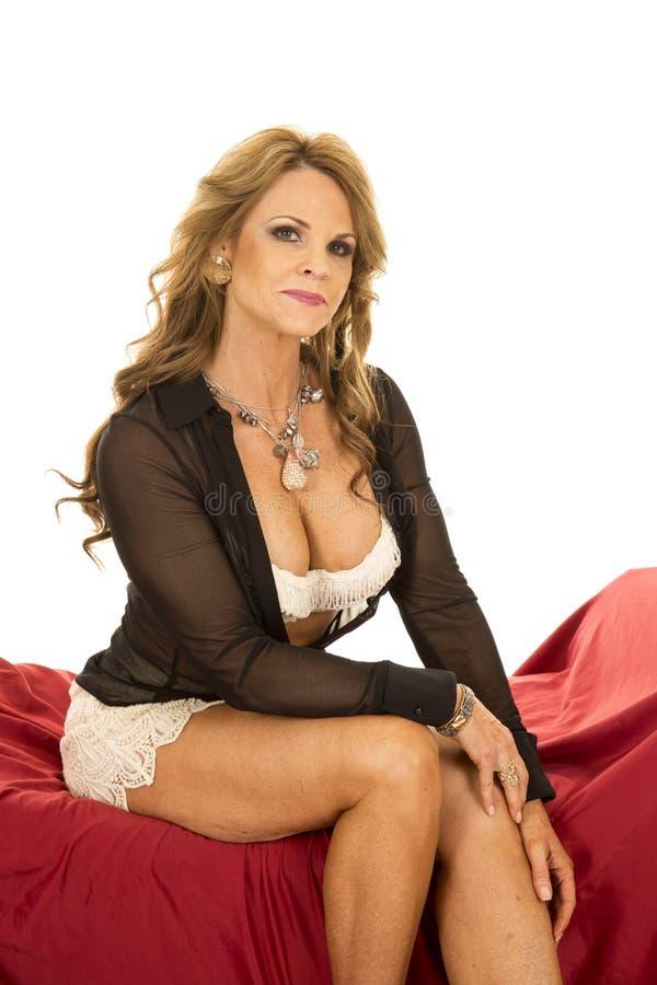 Рубашка бюстгальтера шнурка женщины открытая сидит на красной малой улыбке стоковая фотография
