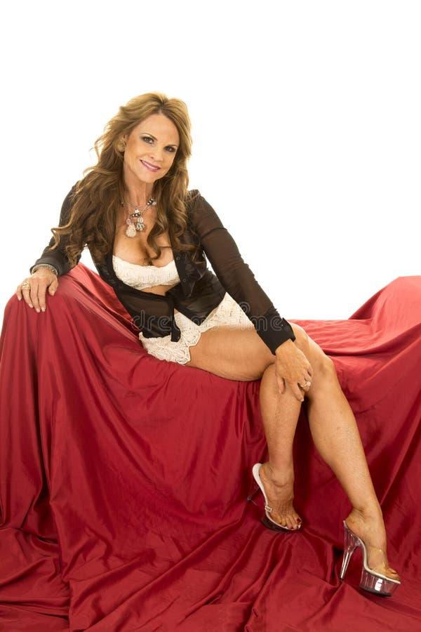 Рубашка бюстгальтера шнурка женщины открытая сидит на красном полном теле стоковая фотография