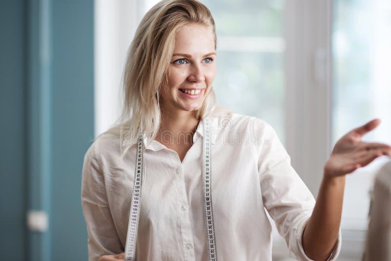 Рубашка выглядящей умн милой белокурой женщины нося белая усмехается с лент-линией на шеи Мода, портной стоковые фото