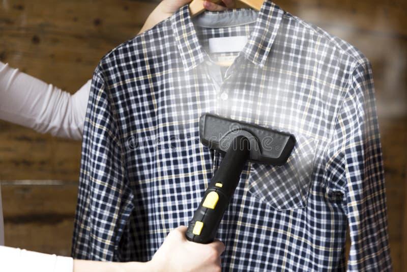 Рубашка женщины утюжа с распаровщиком одежды стоковое фото rf