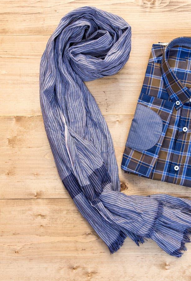 Рубашка и шарф на деревянной доске стоковое изображение