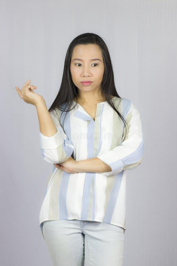 Рубашка коммерсантки нося представляя мысль улыбки изолированную на серой предпосылке стоковые изображения