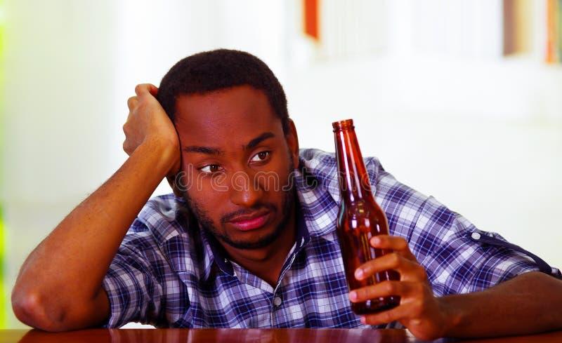 Рубашка красивого человека нося белая голубая сидя лежать бара встречный над столом держа коричневую пивную бутылку, пьяное подав стоковые изображения