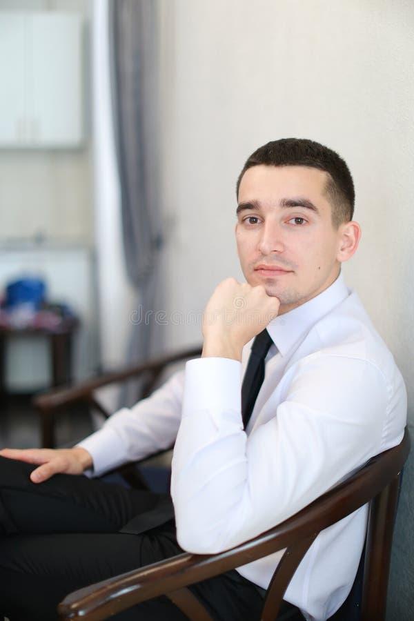 Рубашка молодого красивого бизнесмена нося белая при черный галстук сидя на стуле стоковые фотографии rf