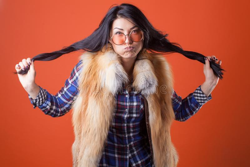 Рубашка шотландки носки представления милой женщины модельные и жилет меха на оранжевой предпосылке студии стоковая фотография