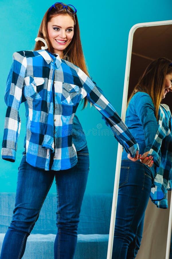 Рубашка шотландки модной женщины пробуя перед зеркалом стоковые фото