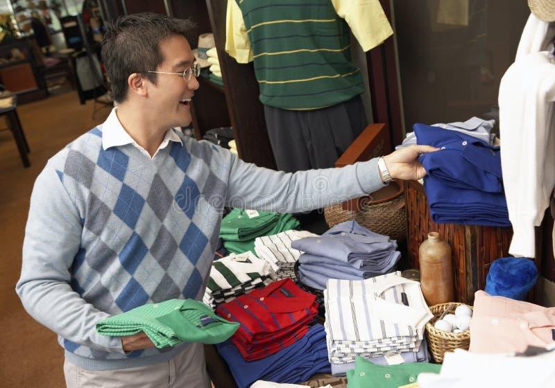 Рубашки счастливого человека покупая стоковое изображение rf