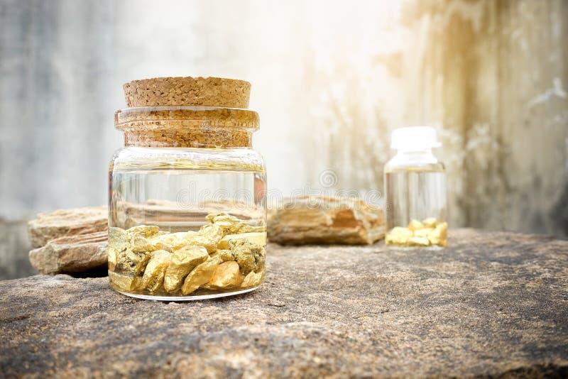 Руда червонного золота нашла в шахтах положенных в стеклянную бутылку стоковые фотографии rf