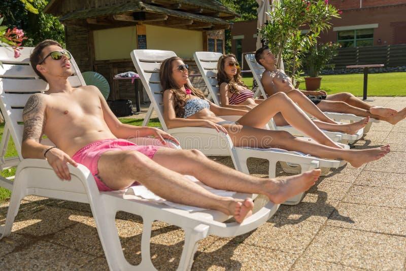 4 друз загорают на loungers солнца на пляже стоковое изображение