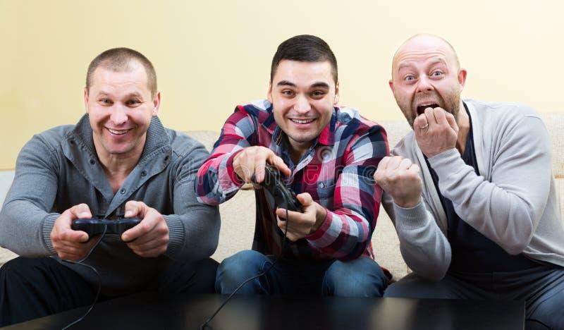 3 друз играя видеоигры стоковые фотографии rf