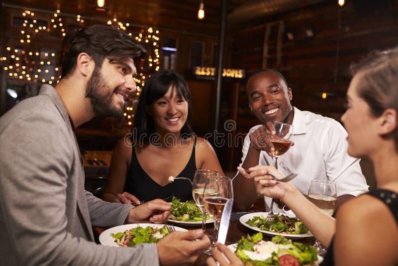 4 друз наслаждаясь обедающим и пить на ресторане стоковое изображение