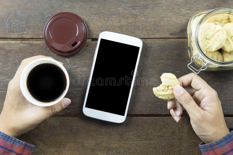 Рука азиатского человека в длинной рубашке держа черный кофе в белом pl стоковое изображение
