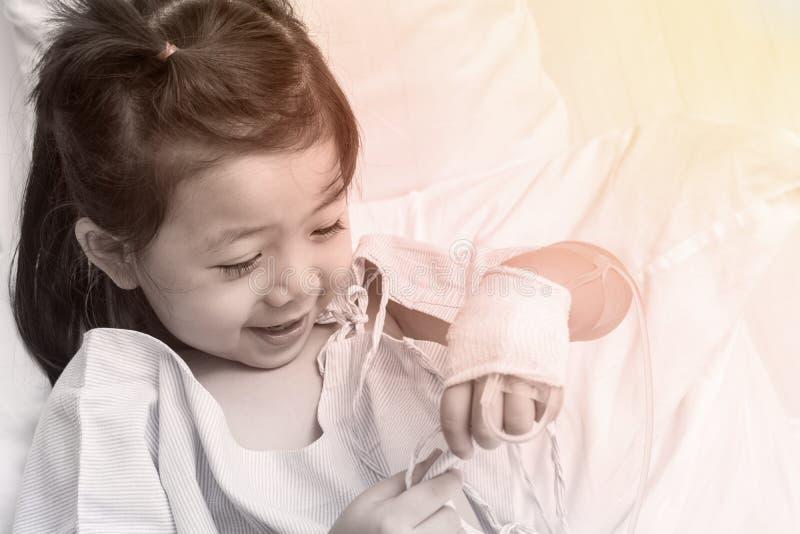 Рука Азии маленькой девочки больного ребенка с физиологическим раствором стоковые фотографии rf