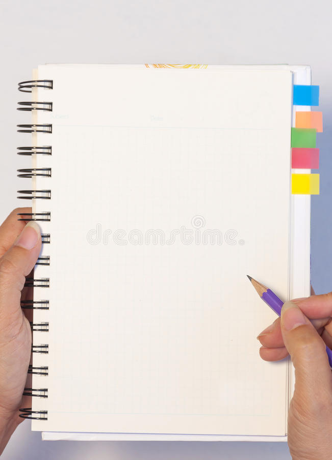 Рука дамы держа карандаш готовый написать пустую тетрадь с липкой памяткой примечания стоковое изображение rf